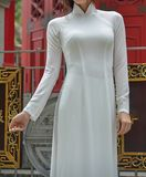 A woman in Vietnamese traditional dress. An Asian woman in Vietnamese traditional dress called Ao Dai standing at Chinese pagoda Royalty Free Stock Photos