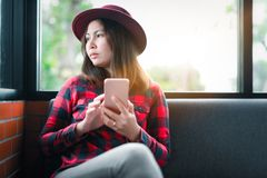 Woman viewed through window of coffee shop using mobile phone stock photos
