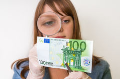 Woman viewing counterfeit banknote with magnifying glass. Woman viewing counterfeit euro banknote with magnifying glass Stock Images