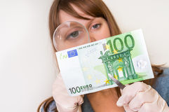 Woman viewing counterfeit banknote with magnifying glass. Woman viewing counterfeit euro banknote with magnifying glass Royalty Free Stock Photography
