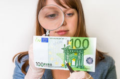 Woman viewing counterfeit banknote with magnifying glass. Woman viewing counterfeit euro banknote with magnifying glass Stock Photos