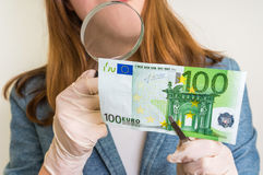 Woman viewing counterfeit banknote with magnifying glass. Woman viewing counterfeit euro banknote with magnifying glass Royalty Free Stock Photo