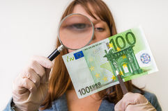 Woman viewing counterfeit banknote with magnifying glass. Woman viewing counterfeit euro banknote with magnifying glass Stock Photo