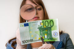 Woman viewing counterfeit banknote with magnifying glass. Woman viewing counterfeit euro banknote with magnifying glass Stock Image