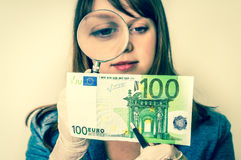 Woman viewing counterfeit banknote with magnifying glass. Woman viewing counterfeit euro banknote with magnifying glass - retro style Stock Photography