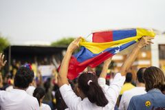 Woman vigorously holding Venezuelan flag at protest royalty free stock photography