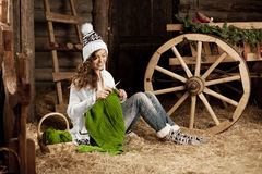Woman in the village barn with knitting in hand Stock Image
