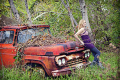 Woman on vinatge truck. A pretty blond woman leaning on an old abandoned truck Royalty Free Stock Images