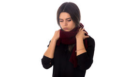 Woman with vinous scarf. Young woman with dark hair in black blouse touching her long vinous scarf and looking down on white background in studio Stock Images