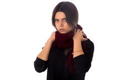 Woman with vinous scarf. Young serious woman with dark hair in black blouse touching her long vinous scarf on white background in studio Royalty Free Stock Photography