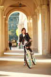 Woman on vintage bicycle in ancient city in light of sunset Royalty Free Stock Images
