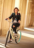 Woman on vintage bicycle in ancient city in light of sunset Stock Photo