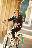 Woman on vintage bicycle in ancient city in light of sunset Stock Images