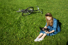 Woman and vintage bicycle, laptop, green lawn, summer. Red hair girl sitting on the grass outside an school, holding a tablet Stock Image