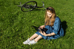 Woman and vintage bicycle, laptop, green lawn, summer. Red hair girl sitting on the grass outside an school, holding a tablet Royalty Free Stock Photo
