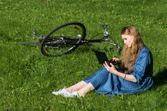 Woman and vintage bicycle, laptop, green lawn, summer. Red hair girl sitting on the grass outside an school, holding a tablet Royalty Free Stock Photography