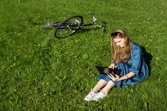 Woman and vintage bicycle, laptop, green lawn, summer. Red hair girl sitting on the grass outside an school, holding a tablet Stock Photo