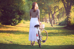 Woman with a vintage bicycle in sunset light Stock Photography