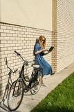 Woman and vintage bicycle and white brick wall, green lawn. Blonde girl is standing outside an office, holding a tablet Stock Photos