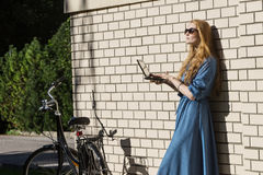 Woman and vintage bicycle and white brick wall, green lawn. Blonde girl is standing outside an office, holding a tablet royalty free stock image