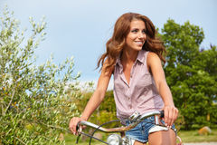 Woman with vintage bike in a country road. Royalty Free Stock Photography