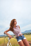 Woman with vintage bike in a country road. Stock Photo
