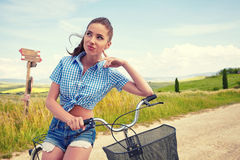 Woman with vintage bike in a country road. Royalty Free Stock Image
