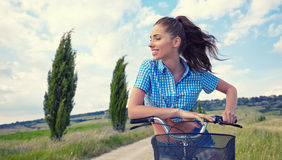 Woman with vintage bike in a country road. Stock Images