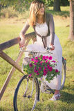 Woman on a vintage bike with flowers Stock Image