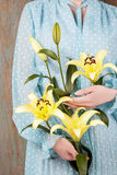 Woman in vintage blue dress holding yellow lily flower. Festive decoration Royalty Free Stock Photos