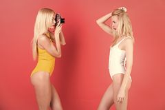 Woman with vintage camera, dieting, fitness. Beauty, fashion, punchy pastels. Hairdresser, new technology. twins women with blonde hair on pink. Girls sister Royalty Free Stock Photography