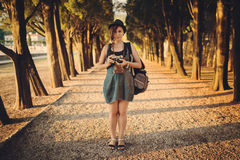 Woman with vintage camera in park alley Royalty Free Stock Photography