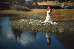 Woman with vintage dress in alpine lake Stock Photo