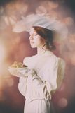 Woman in vintage dress with plate full of chocolates Royalty Free Stock Photo