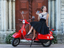 A woman in a vintage dress sitting on a scooter