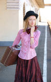 Woman in vintage dress with suitcase Stock Images