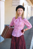 Woman in vintage dress with suitcase Stock Photo