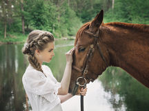 Woman in vintage dress touching to horse face stock photos