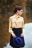 Woman with vintage hat near the river in autumn season. Portrait of young brunette woman with hairstyle in elegant vintage blouse with bow and skirt with Stock Photo