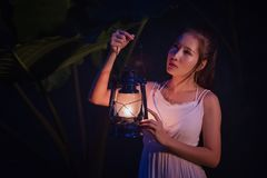 Woman with Vintage Lantern Outside at Night - Cosplay girl in nu Royalty Free Stock Photography