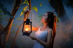 Woman with Vintage Lantern Outside at Night - Cosplay girl in nu Stock Images