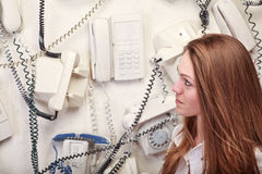 Woman with vintage phones. On wall Royalty Free Stock Images