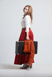Woman in vintage red skirt with a suitcase Stock Photo