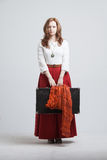 Woman in vintage red skirt with a suitcase Royalty Free Stock Image