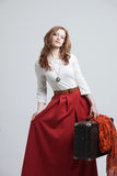 Woman in vintage red skirt with a suitcase Stock Photos