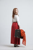 Woman in vintage red skirt with a suitcase Royalty Free Stock Photography