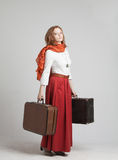 Woman in vintage red skirt with suitcases Royalty Free Stock Image