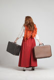 Woman in vintage red skirt with suitcases Stock Images