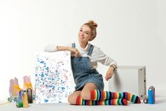 Woman with vintage roller skates, spray paint cans and beautiful picture on white. Background royalty free stock photo