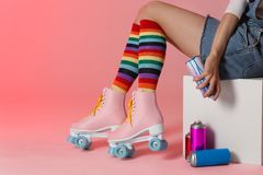 Woman with vintage roller skates and spray paint cans on color background. Space for text. Woman with vintage roller skates and spray paint cans on color stock photo